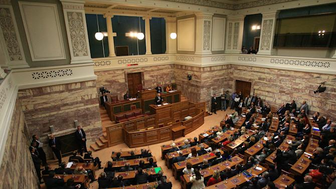Greek Prime Minister George Papandreou, center back, addresses Socialist members of parliament in Athens, Monday, Oct. 31, 2011. Papandreou says his country will hold a referendum on a new European debt deal reached last week. Papandreou gave no date on other details of a proposed referendum on the deal that aims to seek 50 percent losses for private holders of Greek bonds and provide the troubled eurozone member with euro 100 billion ($140 billion) in additional rescue loans. (AP Photo/Thanassis Stavrakis)