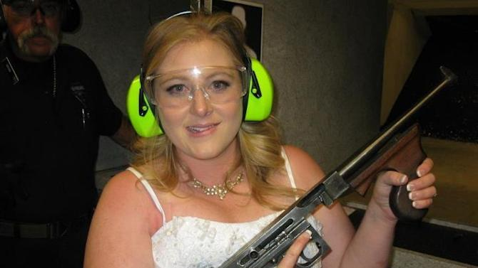 "This July 28, 2012 photo provided by Bob MacDuff shows Lindsae MacDuff holding an automatic weapon at the Gun store in Las Vegas after her ""shotgun wedding."" One Las Vegas shooting range is selling ""take a shot at love"" packages that include 50 submachine gun rounds. Another is offering wedding packages in which the bride and groom can pose with Uzis and ammunition belts. And a third invites lovebirds to renew their vows and shoot a paper cutout zombie in the face. (AP Photo/Bob MacDuff)"