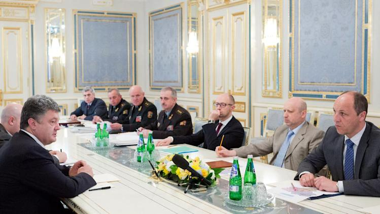 Poroshenko (L) speaks during a meeting of heads of power structures in Kiev, about revoking his one-week unilateral ceasefire on June 24, 2014