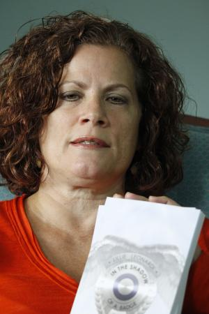 """Lillie Leonardi sits in her living room and shows some copies of her book """"In the Shadow of a Badge: A Spiritual Memoir,"""" on Tuesday, July 3, 2012, in Arnold, Pa. Leonardi, a former police officer who retired from the FBI due to post-traumatic stress disorder from her time as a liaison between law enforcement and the victims of United Airlines Flight 93 has written a book about seeing legions of angels guarding the site where the hijacked airliner crashed on Sept. 11, 2001. (AP Photo/Keith Srakocic)"""