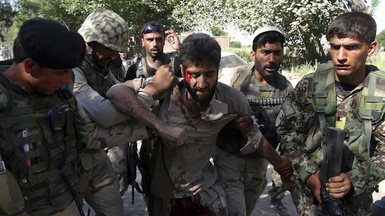 Afghan police carry an injured Taliban fighter, who was captured after an overnight clash with Afghan police in Jalalabad, in the eastern province of Nangrahar, east of Kabul, Afghanistan, Wednesday, June 19, 2013. Provincial police chief Masoon Khan Hashimi said his officers ambushed Taliban insurgents outside a village in the Surkh Rod district, killing several and capturing two. (AP Photo/Nisar Ahmad)