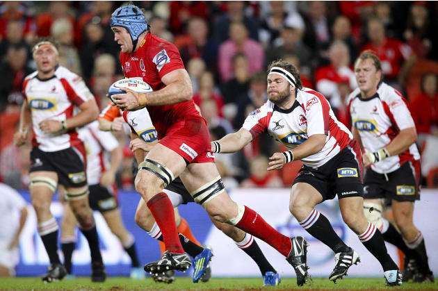 Queensland Reds captain James Horwell (C) runs past Golden Lions hooker Martin Bezuidenhout (R) during their Super 15 rugby union match at Suncorp Stadium in Brisbane on May 19, 2012.  IMAGE STRICTLY