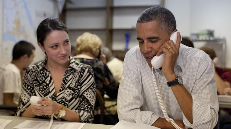 President Barack Obama makes phone calls to volunteers at an Organizing for America field office with Alexa Kissinger, left, Sunday, Oct. 14, 2012, in Williamsburg, Va. (AP Photo/Carolyn Kaster)