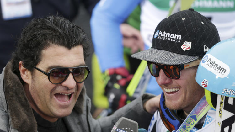 Former Italian skier Alberto Tomba, left, interviews United States's TedLigety after Ligety won the gold medal of the men's giant slalom at the Alpine skiing world championships in Schladming, Austria, Friday, Feb.15,2013. (AP Photo/Matthias Schrader)
