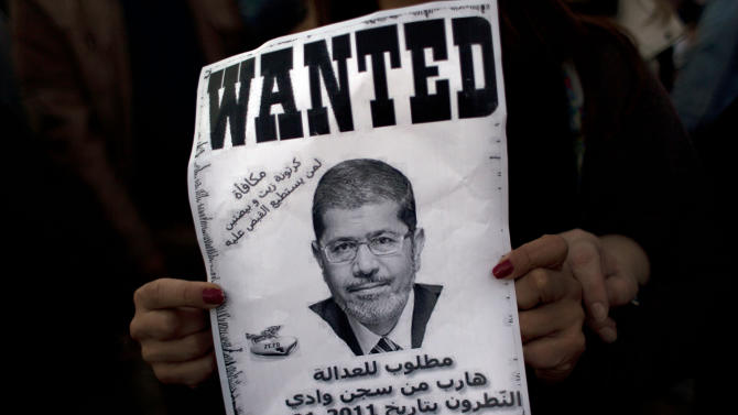 """An Egyptian protester carries a poster with a picture of president Mohammed Morsi and Arabic that reads """"wanted for justice, escaped from the Natroun valley prison in January 29, 2011, Reward, a box of oil and two eggs"""" during an anti-Morsi protest near the presidential palace, in Cairo, Egypt, Friday, Dec. 7, 2012. Egypt's political crisis spiraled deeper into bitterness and recrimination Friday as thousands of Islamist backers of the president vowed vengeance at a funeral for men killed in bloody clashes earlier this week and large crowds of the president's opponents marched on his palace to increase pressure after he rejected their demands. (AP Photo/Nasser Nasser)"""