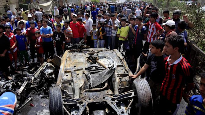 People gather at the scene of a car bomb attack in the Sadr City neighborhood in Baghdad, Iraq, Thursday, May 16, 2013. A car bomb explosion in a sprawling Shiite neighborhood of Baghdad has killed and wounded dozens of people, officials said. (AP Photo/ Karim Kadim)