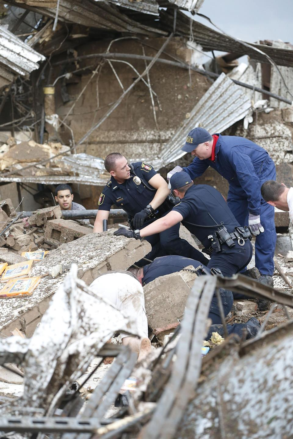 Rescue workers dig through the rubble of a collapsed wall at the Plaza Tower Elementary School to free trapped students in Moore, Okla., following a tornado Monday, May 20, 2013. (AP Photo Sue Ogrocki)