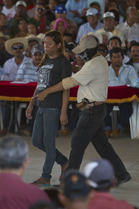 Masked members of the community of Ayutla escort a detained person to a community assembly in the town of El Meson, Mexico, Thursday Jan. 31, 2013. Vigilantes who have taken up arms against drug carte
