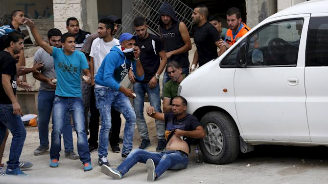 Palestinians try to evacuate a wounded man during clashes with Israeli troops at Qalandia checkpoint near occupied West Bank city of Ramallah