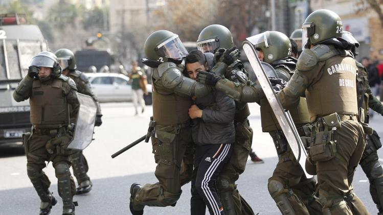 A student is detained by riot police during a demonstration against the government to demand changes in the education system in Valparaiso city