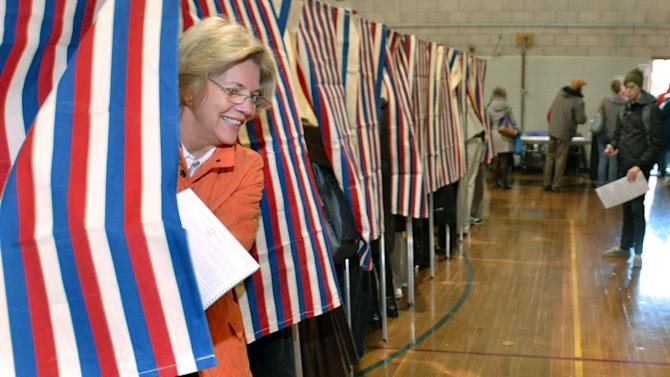 Democratic candidate for U.S. Senate Elizabeth Warren, left, emerges from the polling booth as she votes in Cambridge, Mass. on Election Day, Tuesday, Nov. 6, 2012. Warren is running against Sen. Scott Brown (R-MA), who was elected in a special election in 2010 after the death of Sen. Ted Kennedy (D-MA).  (AP Photo/Josh Reynolds)
