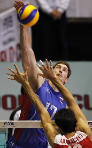 Maxim Mikhaylov of Russia (17) spikes the ball against Arash Kamalvand of Iran during their fourth round match in the men's World Cup volleyball tournament in Tokyo, Saturday, Dec. 3, 2011. (AP Photo/Koji Sasahara)