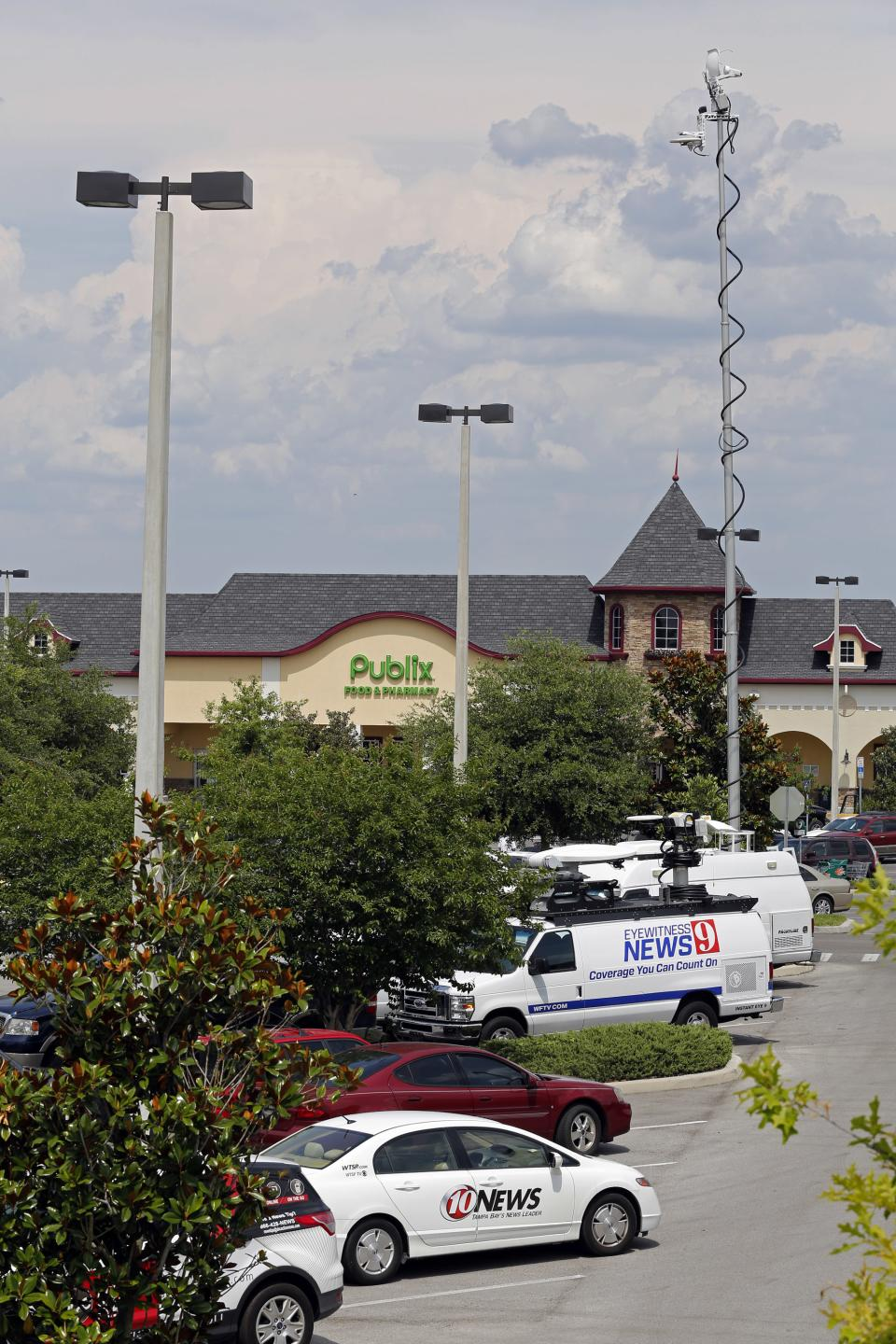 Satellite trucks line the parking lot where the highest Powerball jackpot worth an estimated $590.5 million was sold, at a Publix supermarket in Zephyrhills, Fla. on Sunday, May 19, 2013. (AP Photo/Scott Iskowitz)