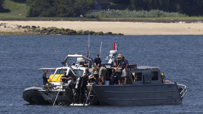 Divers leave the water and come up onto an FBI boat over the site of a sunken yacht near Lloyd Harbor, N.Y., Tuesday, July 10, 2012. FBI divers and New York police say their efforts to retrieve a yacht that capsized and sank, killing three children, will resume Wednesday. The rear end of the boat appears stuck on the seabed floor. The yacht sank July 4 with 27 people onboard following a fireworks display. (AP Photo/Seth Wenig)