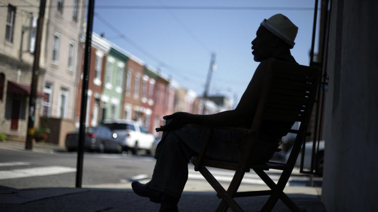 Scoe sits in the shade, avoiding the heat of the sun near his home, Wednesday, July 17, 2013, in Philadelphia. An excessive heat warning is again in effect for the Philadelphia region with highs expected to head up to the mid-90s. (AP Photo/Matt Rourke)