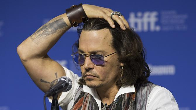 """Actor Johnny Depp gestures a press conference to show his support for the documentary """"West of Memphis"""" at the 2012 Toronto International Film Festival in Toronto on Saturday, Sept. 8, 2012. (AP Photo/The Canadian Press, Michelle Siu)"""