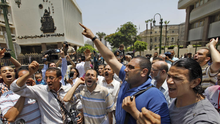 "Egyptian activists shout slogans against military rule in front of the parliament compound in Cairo, Egypt, Tuesday, June 19, 2012.  Egypt's highest court has ordered the country's Islamist-dominated parliament dissolved, saying its election about six months ago was unconstitutional. Arabic reads ""democracy is to ensure sovereignty for people."" (AP Photo/Amr Nabil)"