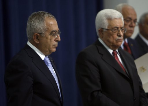 Palestinian Prime Minister Fayyad stands next to President Abbas after Fayyad was sworn-in to the new government in Ramallah