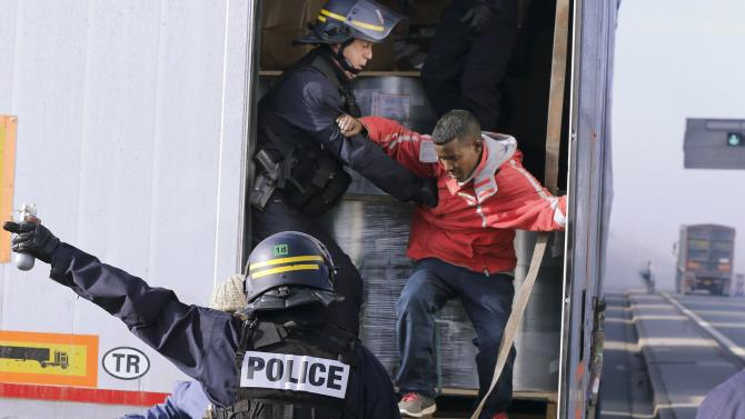 French riot policemen force out migrants who were hidden in a lorry which makes its way to the ferry terminal in Calais