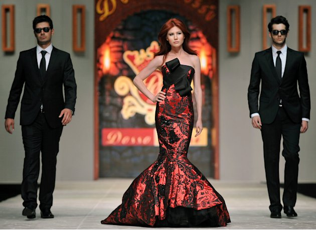 In this photo taken Friday, June 8, 2012, Russian ex-spy Anna Chapman, center, walks a Turkish catwalk flanked by two men posing as secret service agents at a fashion show in Antalya, Turkey. The 30-y