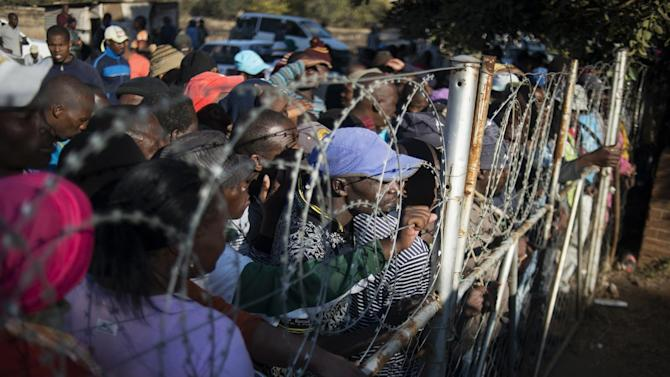 Platinum sector striking miners stand behind a fence and barbed wire as they queue to receive food parcels delivered at the St. Mark church in Marikana, South Africa on June 13, 2014
