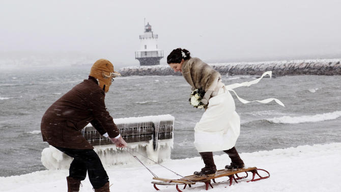 This Saturday, Feb. 9, 2013 photo provided by Bonnie Harrison shows Greg Beal and Karen Willis Beal posing for photos outdoors after their wedding that went on despite a snowstorm in South Portland, Maine. Karen Willis Beal said her vision of a dream wedding included a snowstorm just like the one hit before her parents married in December 1970. The record-breaking storm prevented some of her guests from attending. (AP Photo/Bonnie Harrison)