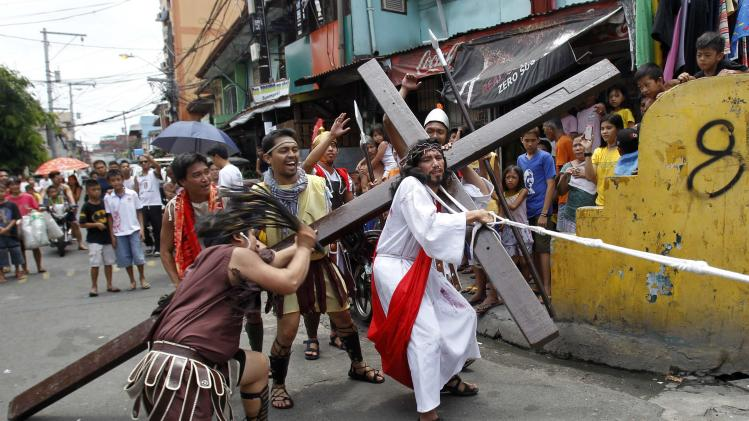 Galvez portrays the role of Jesus Christ as he is whipped by a man dressed as a centurion during a street play of 'Stations of The Cross' on Maundy Thursday in Mandaluyong city, metro Manila