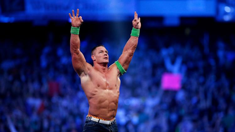 FILE- In this Sunday, April 6, 2014 file photo, John Cena celebrates his win during Wrestlemania XXX at the Mercedes-Benz Super Dome in New Orleans. World-famous WWE wrestlers such as John Cena, Shaemus and champion Randy Orton are in Saudi Arabia for three days of matches in the capital Riyadh. (Jonathan Bachman/AP Images for WWE, File)