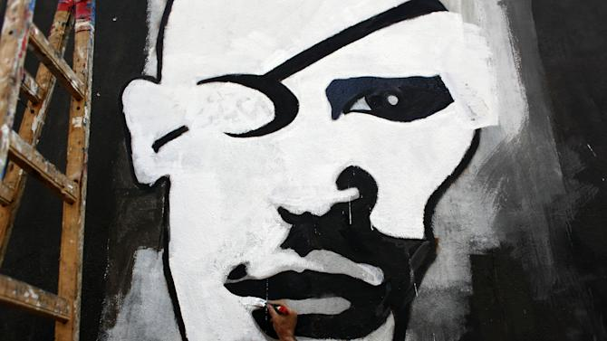 "FILE - In this Sunday. Sept. 30, 2012 file photo, an Egyptian activist artist works on a mural depicting a rebel with an eye patch in Tahrir square, Cairo, Egypt. Graffiti has been among the most powerful art forms and tools of Egypt's revolution and the turbulent months since, but it also has proven to be its most vulnerable and ephemeral. So a group of artists, photographers and a publisher joined hands to preserve the images. ""Wall Talk"" _ their newly released, 680-page book _ collects hundreds of photos of graffiti dating from the Jan. 25, 2011 eruption of the revolt against then-President Hosni Mubarak until today. (AP Photo/Nasser Nasser, File)"