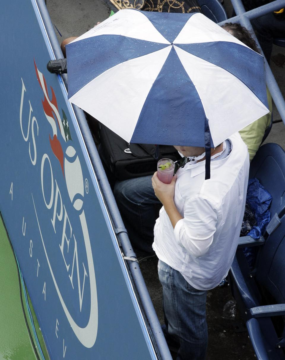 A fan uses an umbrella to stay dry during a rain delay at the U.S. Open tennis tournament in New York, Wednesday, Sept. 7, 2011. (AP Photo/Charlie Riedel)