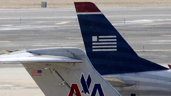 American Airlines and US Airways jets prepare for flight at gate at the Philadelphia International Airport, Thursday, Feb. 14, 2013, in Philadelphia. The merger of US Airways and American Airlines has given birth to a mega airline with more passengers than any other in the world. ( (AP Photo/Matt Rourke)