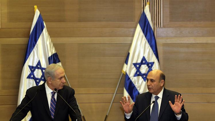 """Israel's Prime Minister Benjamin Netanyahu, left, and Kadima party leader Shaul Mofaz hold a joint press conference announcing the new coalition government, in Jerusalem, Tuesday, May 8, 2012. Netanyahu said Tuesday his new coalition government will promote a """"responsible"""" peace process with the Palestinians. (AP Photo/Sebastian Scheiner)"""