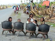 Children await the arrival of relief supplies in New Bataan, Compostela province. Instead of Christmas presents and carols, thousands of people on the island of Mindanao will be more concerned this year with food, water and shelter, civil defence chief Benito Ramos said.