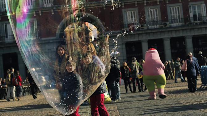 People looks at a bubble breaking in the air as artists perform for money in Madrid, Sunday, Jan. 6, 2013. The number of people registered as unemployed in Spain has gone down, bringing some cheer as the country looks to emerge from recession in 2013. Figures released Thursday showed the registered jobless figure dropped by 59,094 in December compared to November, making for a rounded total of 4.8 million people listed as unemployed. (AP Photo/Andres Kudacki)