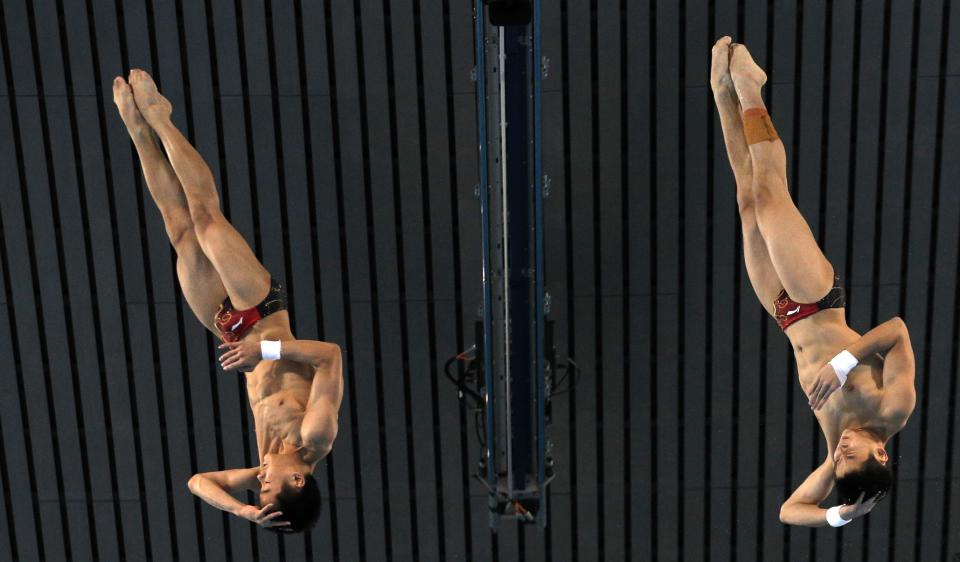Gold medalists Cao Yuan, right, and Zhang Yanquan from China compete during the Men's Synchronized 10 Meter Platform Diving final at the Aquatics Centre in the Olympic Park during the 2012 Summer Olympics in London, Monday, July 30, 2012. (AP Photo/Christophe Ena)