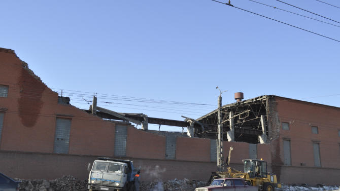 Cars driver psst a zinc factory building with part of its roof collapsed in Chelyabinsk, about 1500 kilometers (930 miles) east of Moscow, Russia, Saturday, Feb. 16, 2013. With a blinding flash and a booming shock wave, a meteor blazed across the western Siberian sky Friday and exploded with the force of 20 atomic bombs, injuring more than 1,000 people as it blasted out windows and spread panic in a city of 1 million.   (AP Photo/Laura Mills)