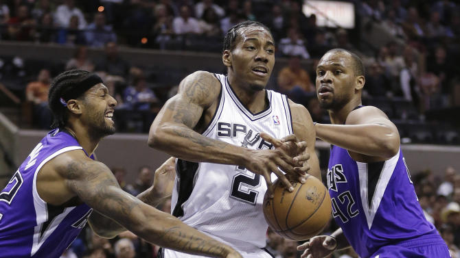 San Antonio Spurs' Kawhi Leonard (2) is striped of the ball by Sacramento Kings' James Johnson, left, as Chuck Hayes, right, also defends against him during the first half of an NBA basketball game on Friday, March 1, 2013, in San Antonio. (AP Photo/Eric Gay)