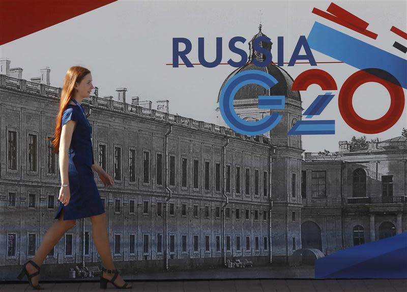 An employee passes by a sign at the main press centre of the G20 summit in Strelna near St. Petersburg
