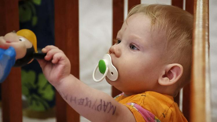 A child, whose name is written on arm, plays with a toy in a crib in an orphanage in Kramatorsk