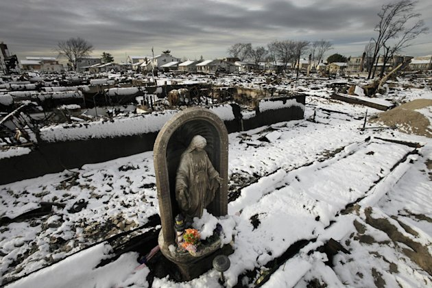 A religious statue stands in the fire-scorched landscape of Breezy Point after a Nor'easter snow, Thursday, Nov. 8, 2012 in New York.  The beachfront neighborhood was devastated during Superstorm Sand