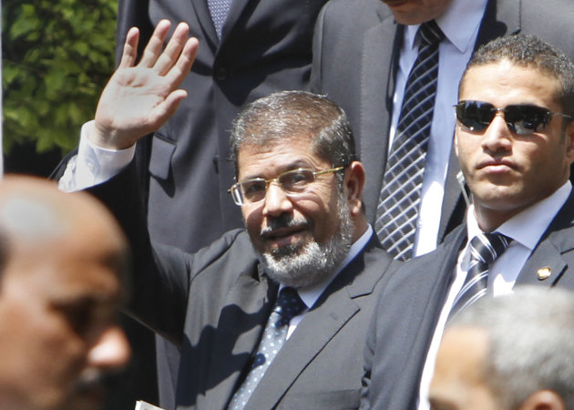 Egyptian President Mohammed Morsi waves to photographers as he leaves the Arab League headquarters in Cairo, Egypt, Wednesday, Sept. 5, 2012. Morsi says Syrian leader Bashar Assad must learn from &quot;recent history&quot; and step down before it is too late. (AP Photo/Amr Nabil)