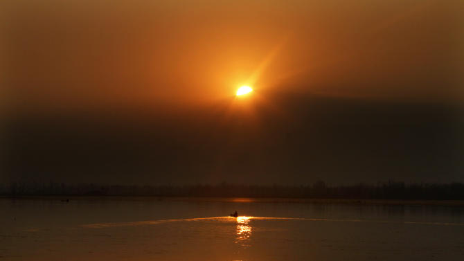 A Kashmiri boatman rows during the last sunset of the year 2012 at the Dal Lake in Srinagar, India, Monday, Dec. 31, 2012.(AP Photo/Mukhtar Khan)