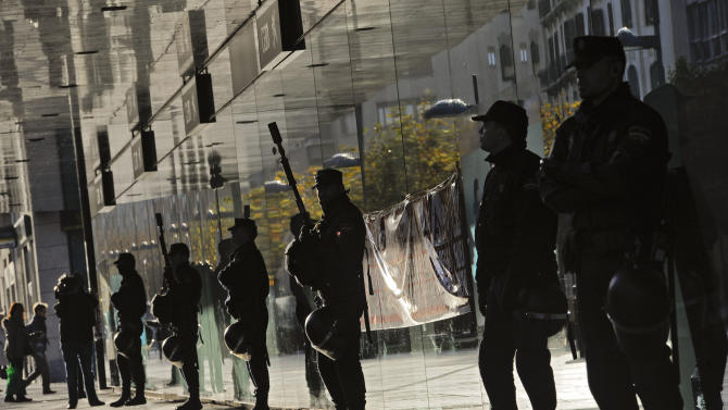 Spanish riot policemen stand in a line against the window of a bank during a general strike against government austerity measures, in Pamplona, northern Spain, Wednesday, Nov. 14, 2012. A Spanish Interior Ministry official says 32 people have been arrested and 15 people treated for minor injuries in disturbances as a general strike in Spain against austerity measures and economic reforms began. The General Workers Union said the nationwide stoppage, the second this year, was being heeded by nearly 100 percent of workers Wednesday in the automobile, energy, shipbuilding and constructions industries. (AP Photo/Alvaro Barrientos)