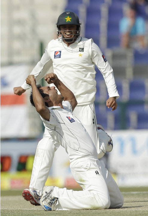 Pakistan's Abdur Rehman, ground, celebrates taking the wicket of England's Kevin Pietersen, not pictured, lbw as his teammate Azhar Ali runs during the fourth day of the second cricket Test match of a