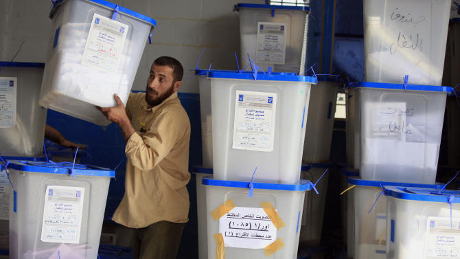 An electoral worker carries a ballot box at a counting center in Baghdad, Iraq, Sunday, April 21, 2013. Iraqis have begun counting votes from the first provincial elections since the last U.S. troops withdrew in December 2011. (AP Photo/ Karim Kadim)