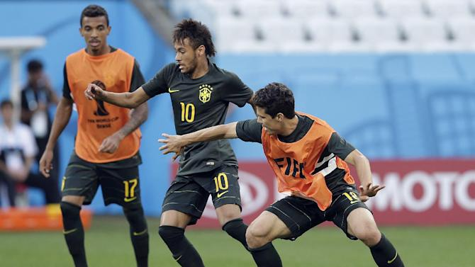 Brazil's Luiz Gustavo, from left, Brazil's Neymar and Brazil's Hernanes challenge for the ball during an official training session the day before the group A World Cup soccer match between Brazil and Croatia in the Itaquerao Stadium, Sao Paulo       , Brazil, Wednesday, June 11, 2014
