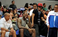 Two-time NBA champion LeBron James (C) of the Miami Heat laughs on the bench as he coaches Filipino basketball players during a clinic at the Mall of Asia Arena in Manila on July 23, 2013