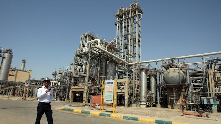 FILE - In this Wednesday, Sept. 28, 2011 file photo, an Iranian security guard stands at the Maroun Petrochemical plant at the Imam Khomeini port, southwestern Iran. Iranian officials unleashed sharper attacks against tightening Western sanctions Tuesday, equating the financial pressure to ``warfare'' and vowing to counter by retooling the country's oil-dependent economy. (AP Photo/Vahid Salemi, File)