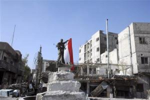 A soldier loyal to Syria's President Bashar al-Assad poses with the national flag in Hujaira town, south of Damascus, after the soldiers took control of it from the rebel fighters,in this handout photograph distributed by SANA