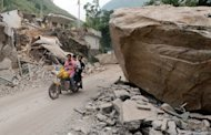 Local residents ride past a house that was destroyed by a landslide after a series of earthquakes hit Yunnan Province. Rescuers searching for survivors from twin earthquakes that struck southwestern China battled blocked roads and downed communications as the death toll rose to 80
